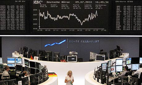 Traders work at their desks in front of the the DAX board at the Frankfurt stock exchange