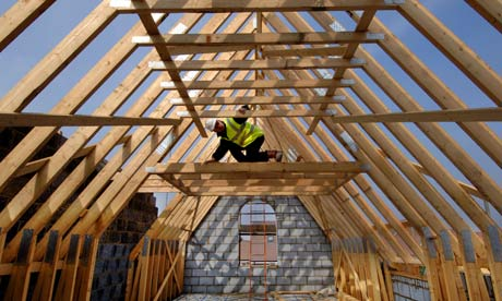 A builder surveying the roof timbers of a new house under construction.