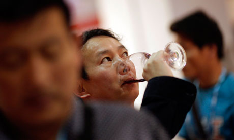 A man drinks Sarome Bordeaux vineyard from France at the 6th Shanghai International Wine Trade Fair