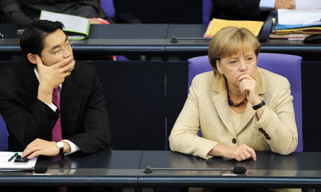 Economy Minister Philipp Roesler (L) and Chancellor Angela Merkel (R) wait at the Bundestag