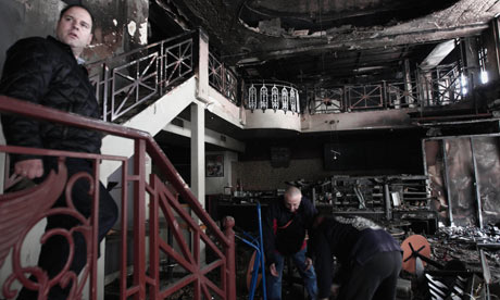 Workers clear a burned out cafe in central Athens on Monday February 13, 2012.