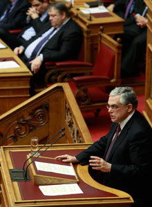 PM Papademos addresses lawmakers during a parliament session before a vote for a new austerity deal.