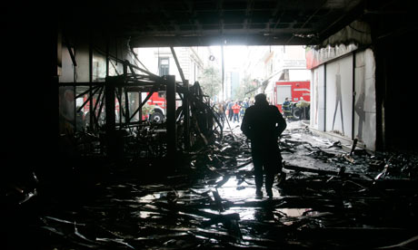 A man walks inside the burnt atrium of a mall after violence in Greece, on 13 February 2012.