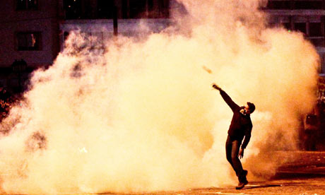 A protester throws an object back toward riot police during riots in Athens, on12 Febuary 2012.