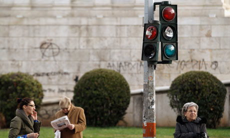 Commuters are seen around a destroyed traffic light after violent protest in Athens, 14 Feb 2012.