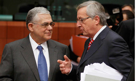 Jean-Claude Juncker talks with Greece's PM Papademos at the start of a Eurogroup meeting in Brussels