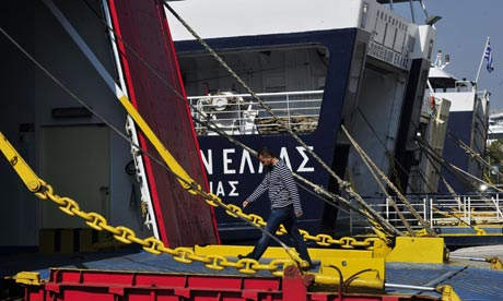A worker walks into an anchored ferry in the harbour of Piraeus near Athens.