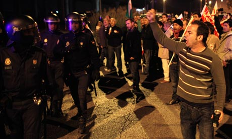 Union picketers shout slogans to riot police officers at the start of a general strike in Malaga