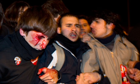 A man is seen bleeding after being struck by police during a national strike in Madrid.