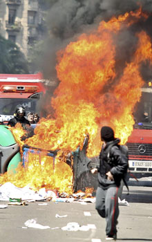 A man moves away from a burning trash bin in Barcelona, Spain, 29 March 2012 during a general strike