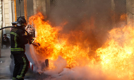 A firefighter extinguishes a fire during a general strike in central Barcelona