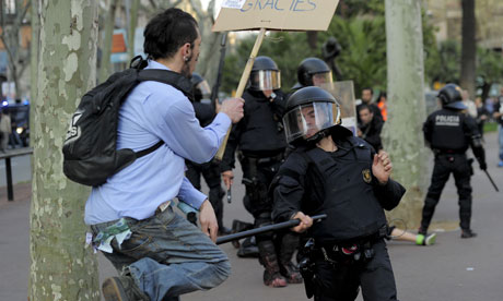 A protester clashes with a with riot policeman during a demonstration in Barcelona
