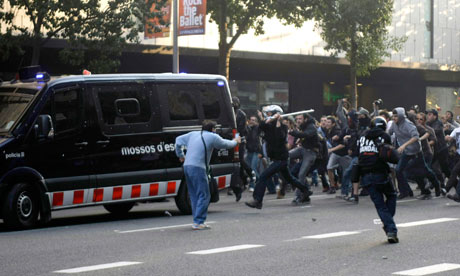 Protesters attack a police van during a general strike in central Barcelona