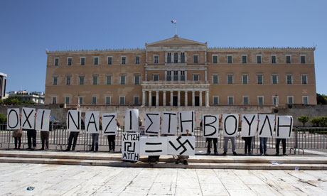 Protesters hold placards reading ''No Nazis in Parliament, Golden Dawn=Swastika''.