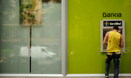 A man uses a Bankia ATM machine on May 17, 2012 in Madrid.
