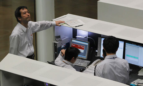 Tokyo Stock Exchange employees look at monitors at the bourse in Tokyo
