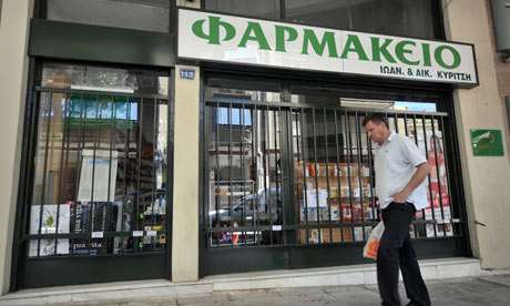A man walks past a closed pharmacy in Athen.