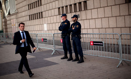 Police officers stand guard ahead of the European Central Bank meeting in Barcelona.