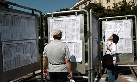 Two people checks lists of electoral candidates in Athens ahead of Sunday's general election.