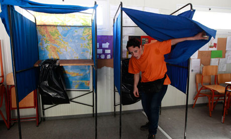 A municipality worker comes out of a voting booth at a voting centre in Athens
