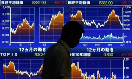 A man walks past a board showing graphs of Japan's stock price indexes outside a brokerage in Tokyo