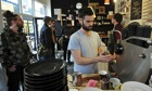 A man makes coffee at a boutique cafe in Brixton