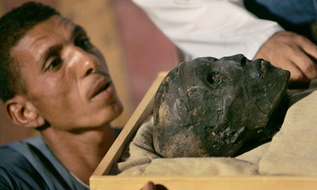 Archaeological worker looks at mummy of King Tutankhamun