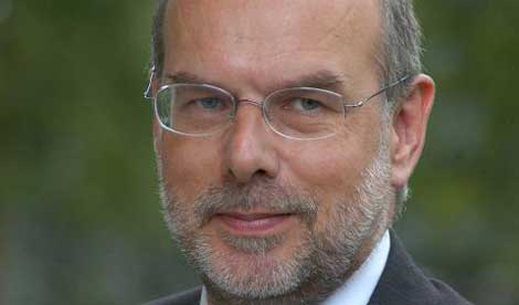 A close-up photograph of David Eastwood; a man with receding grey hair, and grey moustache and beard, wearing rimless glasses and a neutral facial expression.