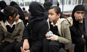 Pupils, some wearing Muslim headscarves, in the playground at Grange School in Oldham