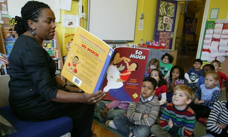 Teacher reads to infant school class