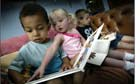 Children look at books at nursery