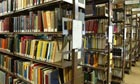 A student looking at shelves of books in the library of Leicester University.