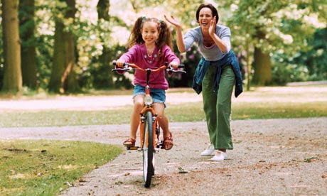 Girl riding a bicycle, mother applauding