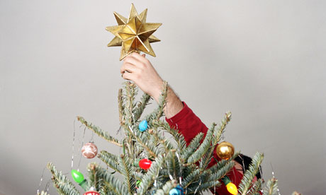 putting star on christmas tree