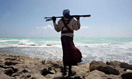 A Somali pirate stands on the coastline