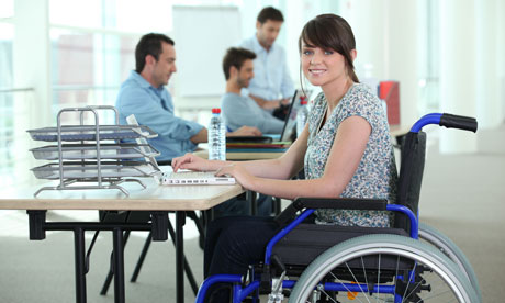 Young woman in wheelchair with laptop computer