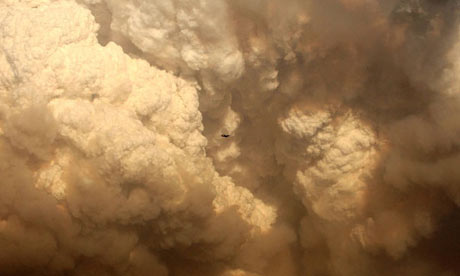 A Boeing 737 flies by a massive smoke plume over Kinglake