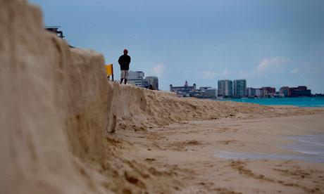 COP16 Cancun : A man stands on a eroded beach