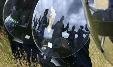 Eco-activists reflected in a Police riot shield  at the Climate Camp near Kingsnorth Power Station
