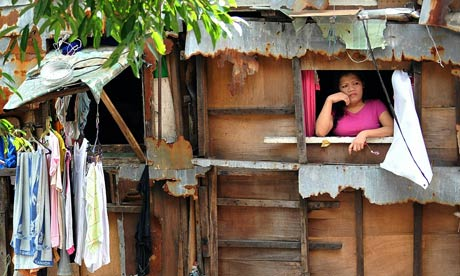 MDG : A woman (R) gazes out from a window in one of Manila's slum