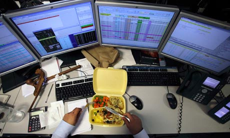 A dealer eats his lunch as he monitors his screens on the trading floor of IG Index in London