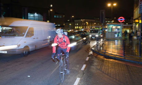 A cyclist at night outside Kings Cross London UK