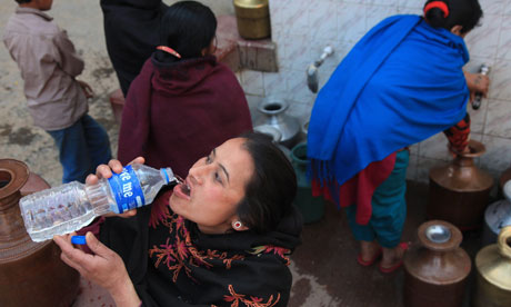 A Nepalese woman drinks water while waiting for others to fill their pots in Kathmandu