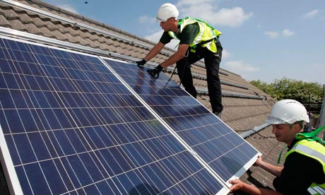 Workmen install HomeSun solar panels on to the roofs of homes on a street in Delabole in Cornwall