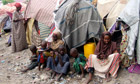 MDG : Somalia : Somalis frefugees so sit outside their makeshift home in Mogadishu