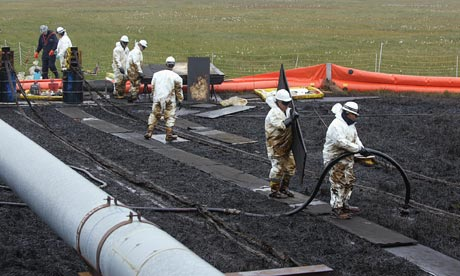 Workers clean up an oilspill at BP Pudhoe Bay oil fields in Alaska
