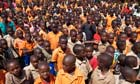 MDG : Rwanda : School children stand in their playground waiting for instructions