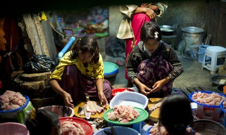 MDG : Child labour : Young girls clean fish at a central fish market Yangoon, Myanmar