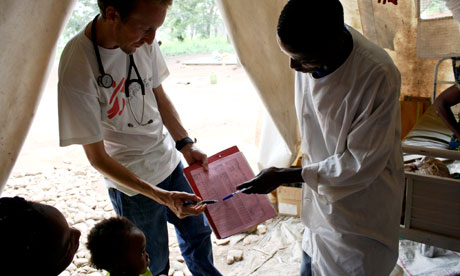 MDG: Dr Chris Bird (L) and a nurse show a mother a record of her child's weight gain, DRC