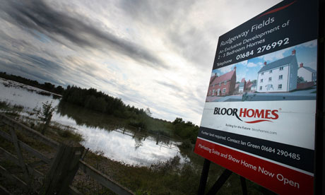 Planning system reforms :  A sign in a flooded field advertises for new houses in Tewkesbury